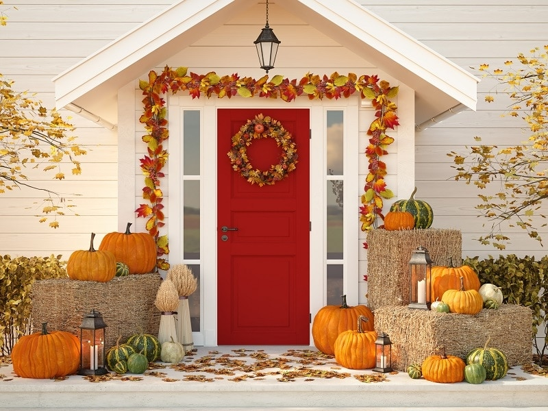 Front door decorated for autumn with pumpkins and hay