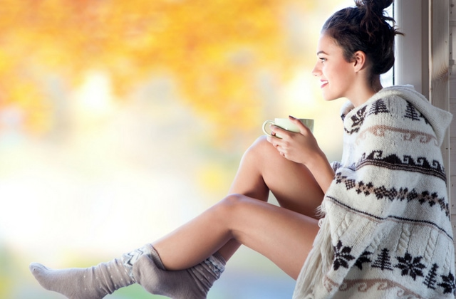 Woman wearing a cardigan and cozy socks sitting in the Autumn sunlight with a cup of cocoa enjoying the view